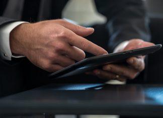 Businessman in formal suit navigating a huawei tablet