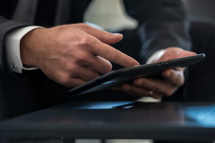 Businessman in formal suit navigating a huawei tablet