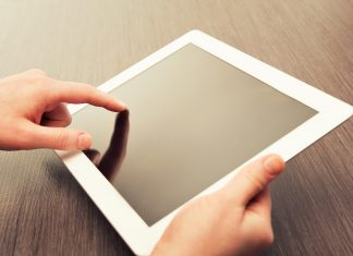 white tablet with a blank screen in the hands on table - google tablet