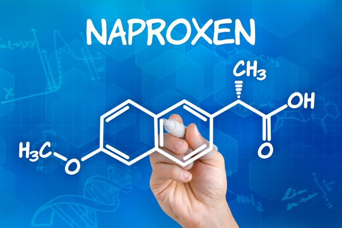 Hand with pen drawing the chemical formula of naproxen