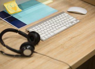 Headphones and computer on a wooden Desktop.