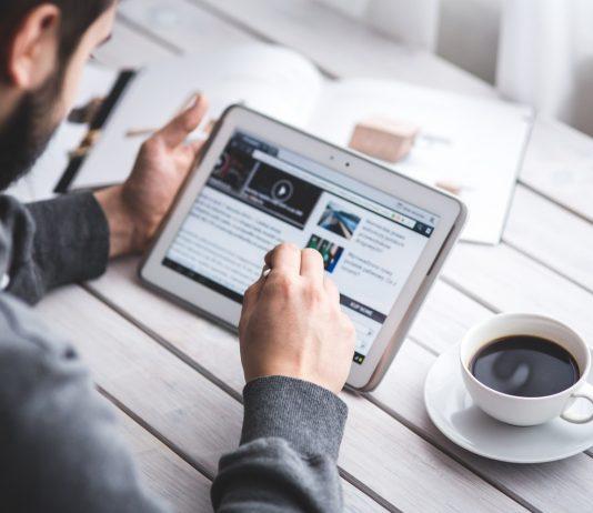 Man usinga tablet near a coffee