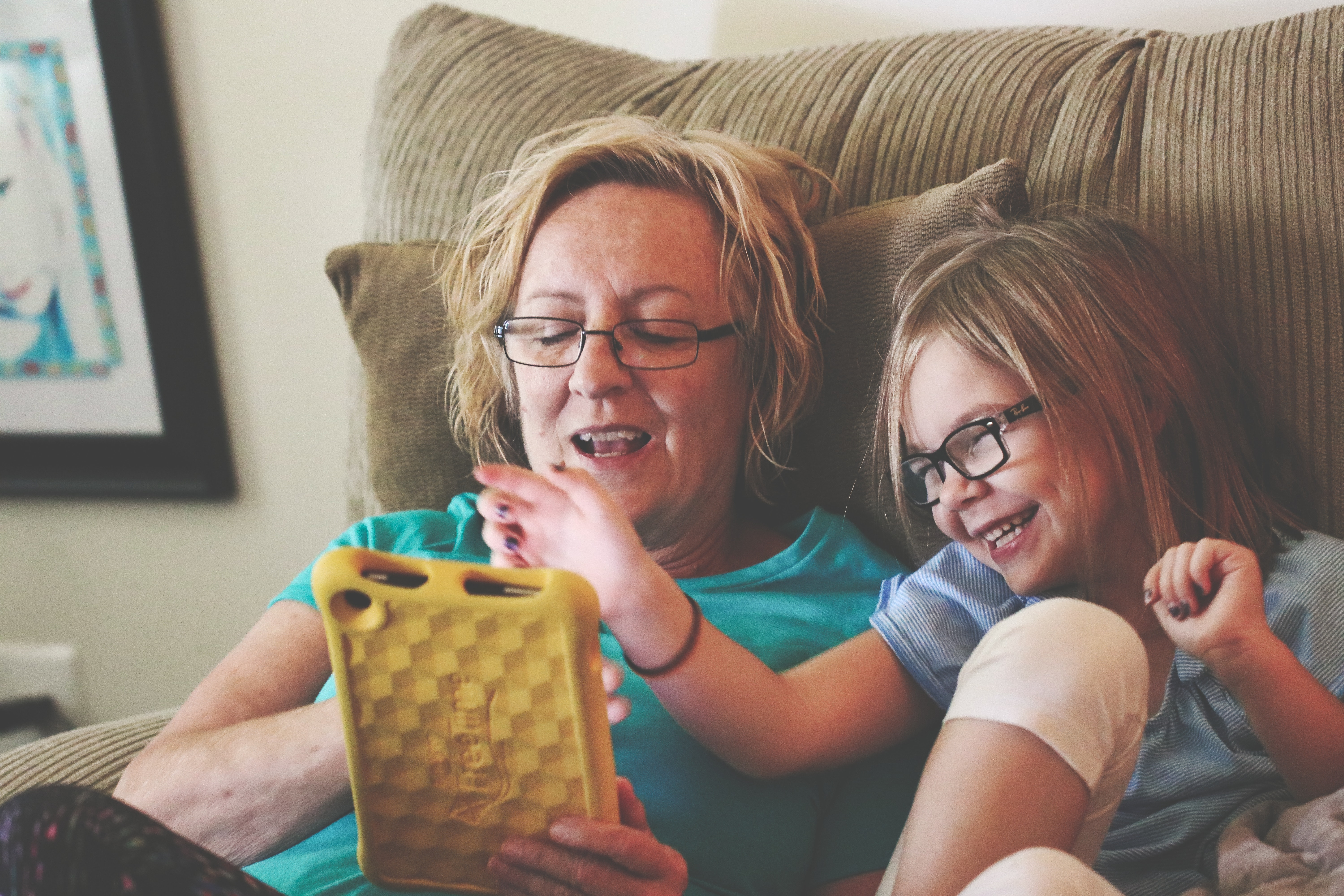 adult and  child enjoy while using tablet computer