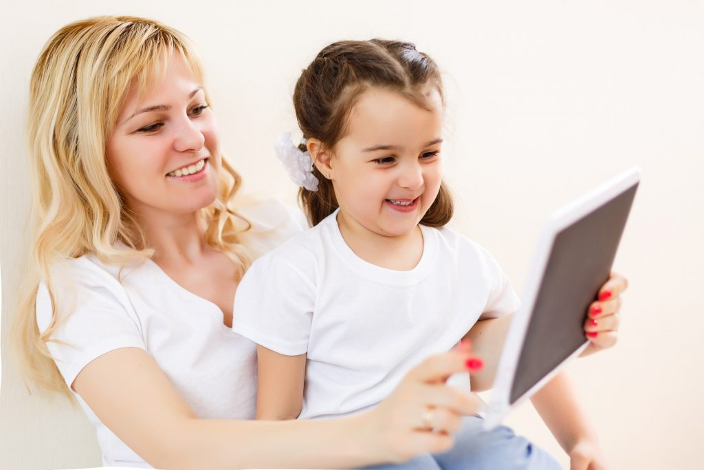 A mom and daughter look at a tablet that is protected by one of the best kid's tablet cases.